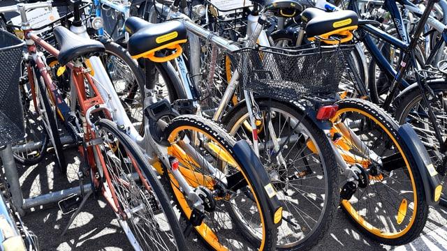 öffentlicher Veloständer mit zwei orangen O-Bikes zwischen anderen Fahrrädern