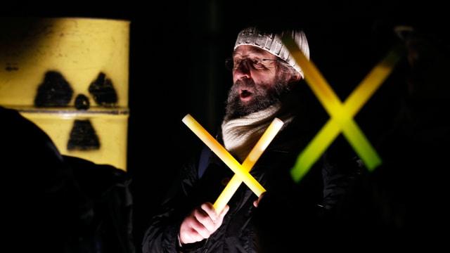 Ein Mann steht vor einer gelben Tonne und hält ein leuchtendes, gelbes Kreuz in der Hand.