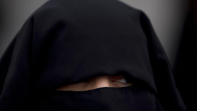 Eine Muslima mit einem schwarzen Kopftuch, das nur ihre Augen frei gibt.