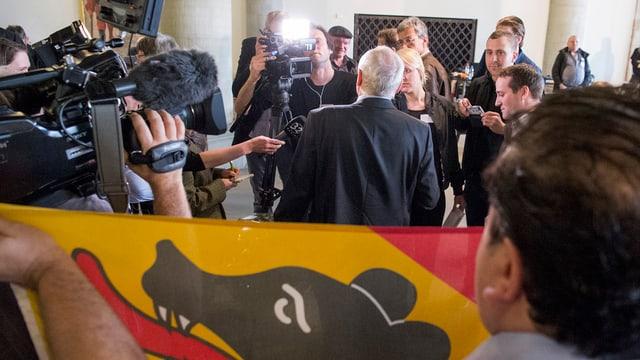 Ein Gewählter im Scheinwerferlicht - davor eine Berner Fahne.