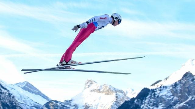 Skispringer vor Bergkulisse