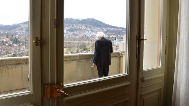 Mann steht mit Zigarette auf Balkon. Fensterrahmen.