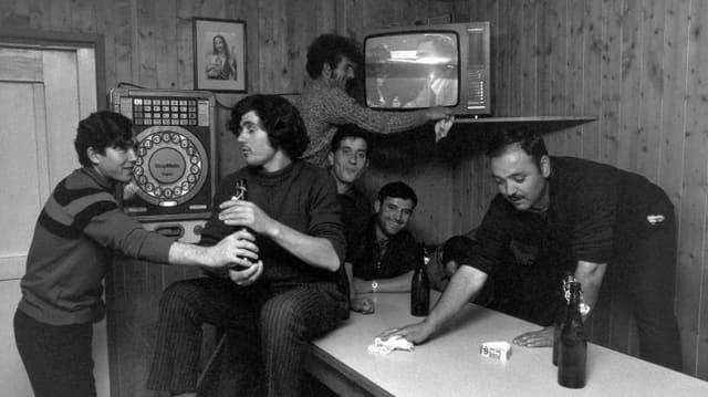 eine schwarz-weiss Fotografie von Männern, die auf einem Tisch sitzen und einer putzt den Tisch
