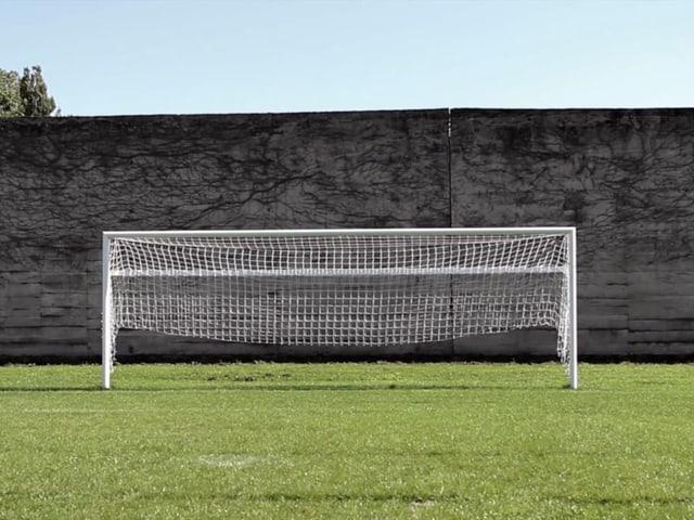 Fussballtor vor einer hohen grauen Wand.