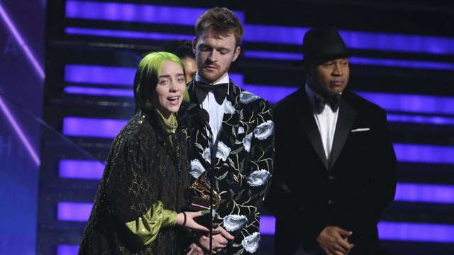 Purtret da Billie Eilish e ses frar Finneas sin tribuna, Billie tegna il premi e discurra en il microfon fertant che ses frar stat dasper ella.