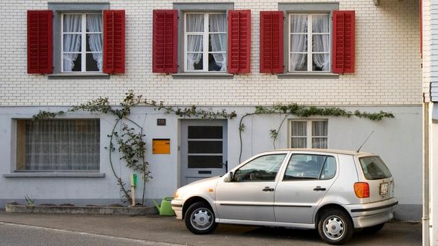 Ein Auto parkiert vor einem Haus.