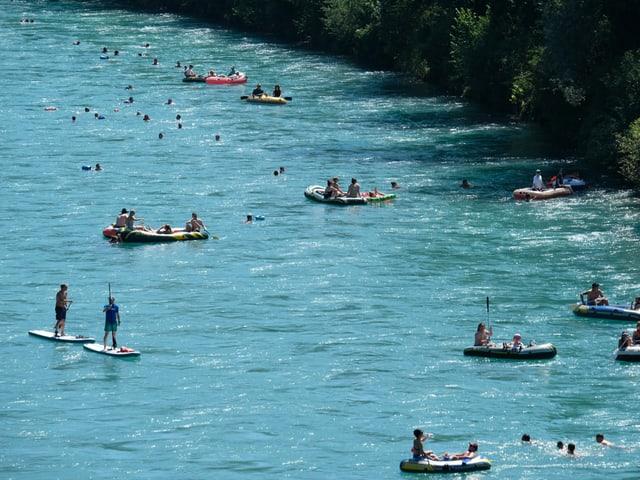 Boote und Schwimmer in einem Fluss