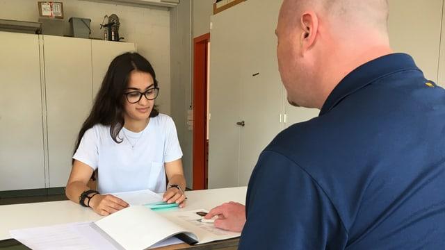 Schülerin sitzt am Tisch mit Mann, beide schauen auf ein Dossier das auf dem Tisch liegt.