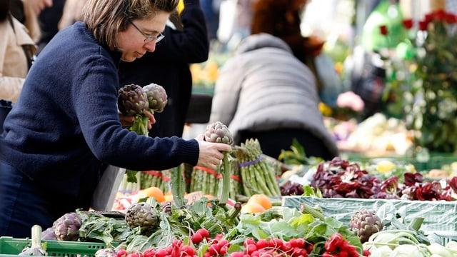 Frau sucht Gemüse an Stand