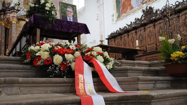 Ein rot-weisse Schleife am Kranz, der mit roten und weissen Blumen geschmückt ist. Im Hintergrund der Tisch mit dem Bild von Peter Zwick.