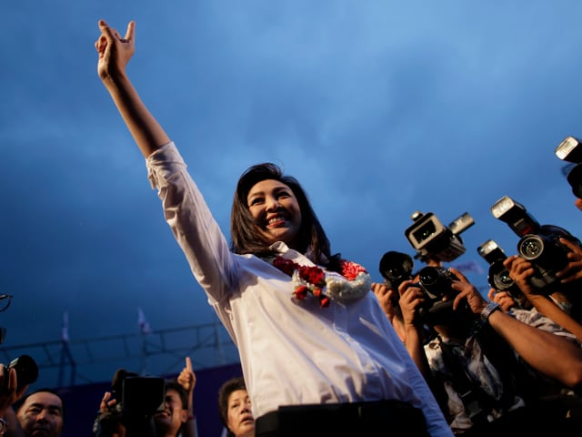 Yingluck Shinawatra in Siegerpose vor Reportern