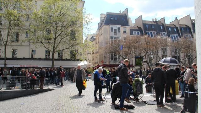 Blera glieud avant il museum Centre Pompidou. Els sesan, batarlan e s'inscuntran.