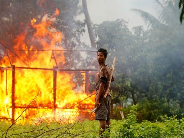 Ein Mann mit Waffe vor brennender Hütte.