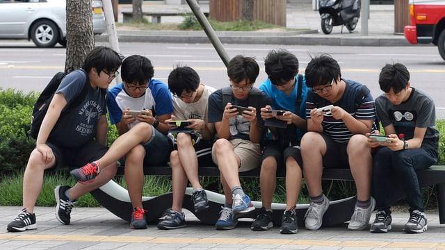 Giuvens en la Corea dal sid vi da lur smartphones.