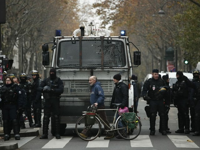 Polizisten in Vollmontur stehen in Reih und Glied. Menschen laufen davor herum.
