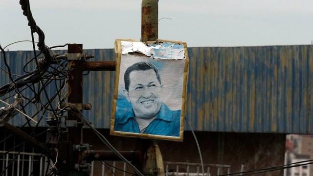 Wahlplakat mit Chavez-Konterfei hängt an einem Strommasten.