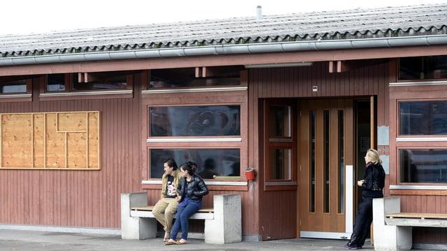 Drei Personen stehen vor em Eingang einer Holzbaracke