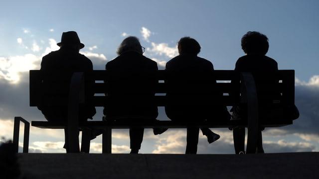 Vier Rentner sitzen auf einer Bank.