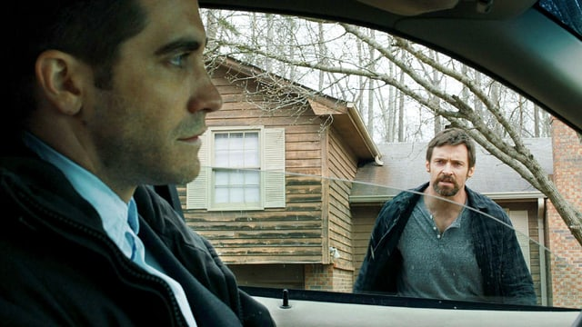 Ein Mann sitzt im Auto, ein anderer mann läuft seitlich auf das Auto zu.