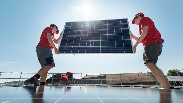 Männer montieren eine Solaranlage.