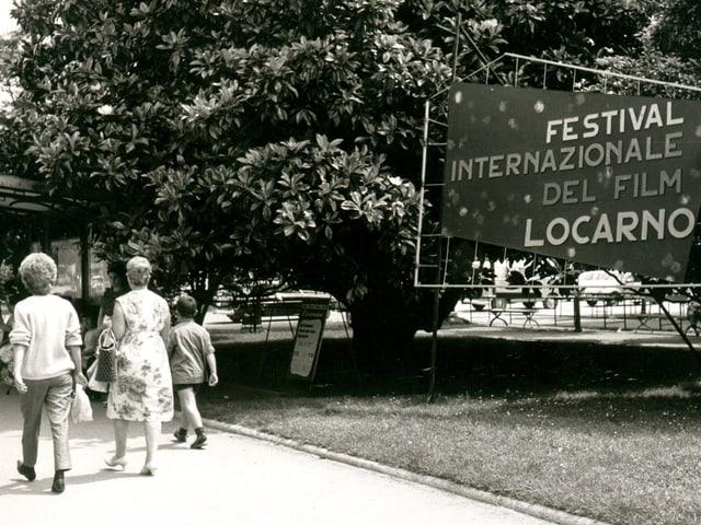 Zwei Frauen gehen 1963 am Logo des Festivals vorbei.