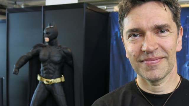 Enrico Marini schaut in die Kamera, im Hintergrund sieht man eine Batman-Figur.
