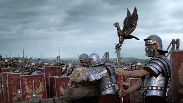 Römische Soldaten auf einem Schlachtfeld, zwei Männer laden ein Katapult.