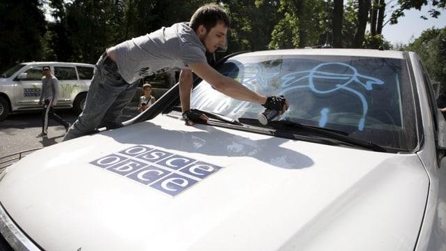 Mann sprayt auf Scheibe von OSZE-Auto