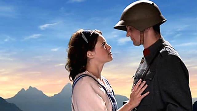 Ein Soldat und seine Frau stehen sich gegenüber. Ihre Hand liegt auf seiner Brust. Im Hintergrund sieht man einen See und Berge bei Sonnenuntergang.