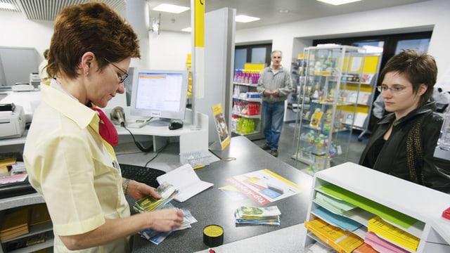 Eine Postangestellte bedient eine Kundin am Schalter