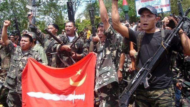 Schwer bewaffnete Männer in Tarnuniformen skandieren Slogans.