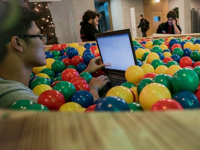 Zwei Männer mit Computern sitzen in farbigen Plastikbällchen