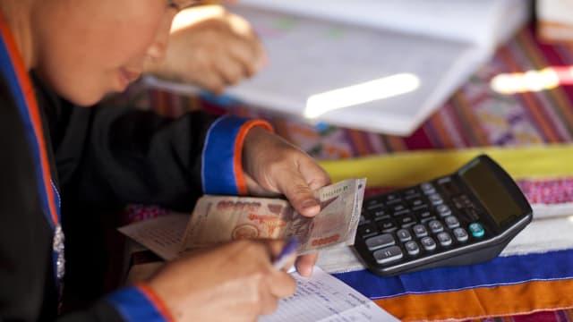 Asiatisches Mädchen zählt Geld vor Taschenrechner