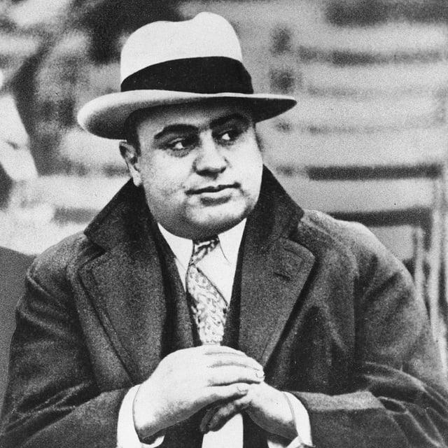 Gangsterboss Al Capone mit Hut und Mantel.