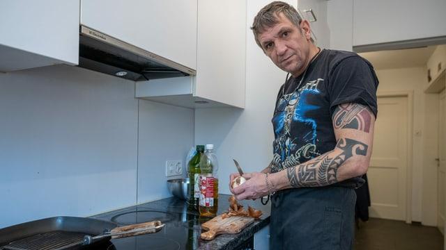 Ein Mann schneidet in der Küche eine Zwiebel und blickt in die Kamera. Am Unterarm ist er tätowiert.