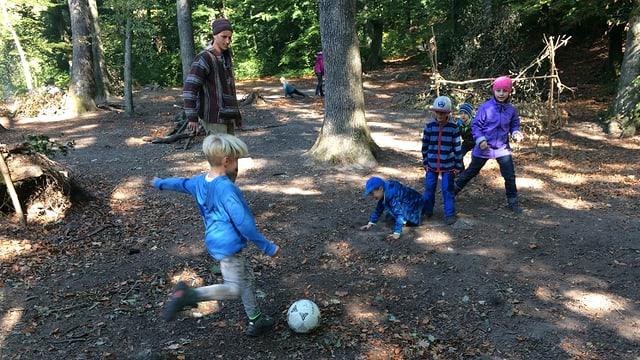 Kinder spielen im Wald Fussball.