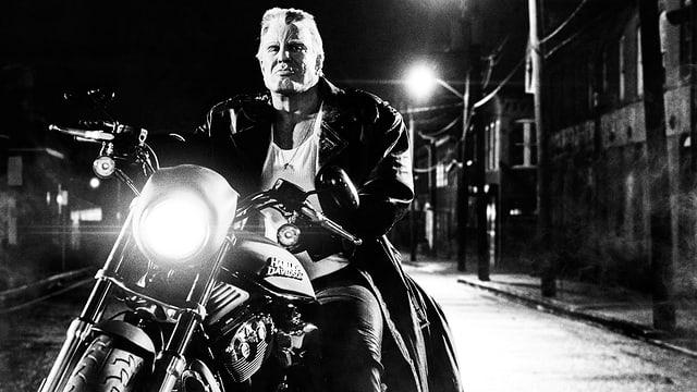 Ein grosser, grimmiger und muskulöser Mann sitzt auf einem Motorrad.