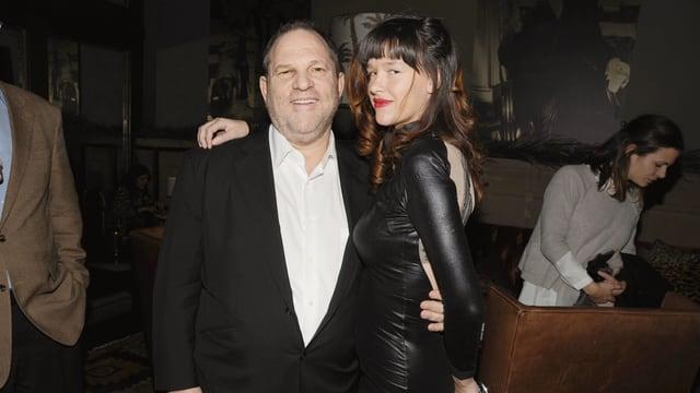 Weinstein links in seinem Arm Schauspielerin in schwarz.