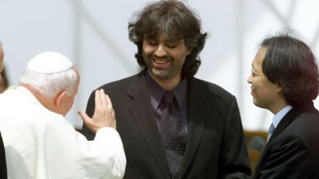 Andrea Bocelli steht vor dem Papst. Dieser trägt sein klassisch weisses Gewand während Bocelli einen schwarzen Anzug anhat.