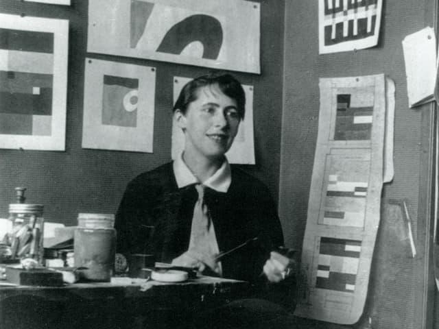 Sophie Taeuber an einem Tisch sitzend, hinter ihr Bilder von Ihr an der Wand.