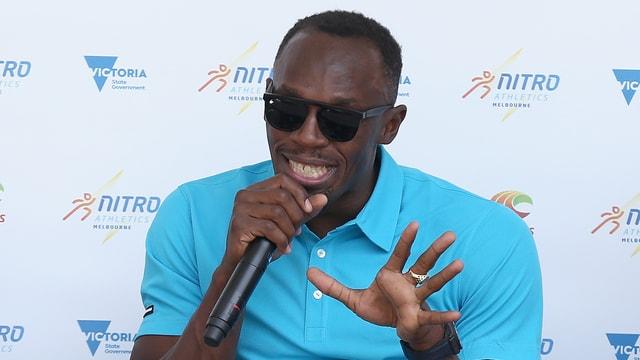 Usain Bolt mit Mikrofon in der Hand