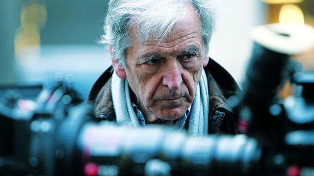 Der Regisseurs Costa-Gavras blickt konzentriert auf eine Kamera.