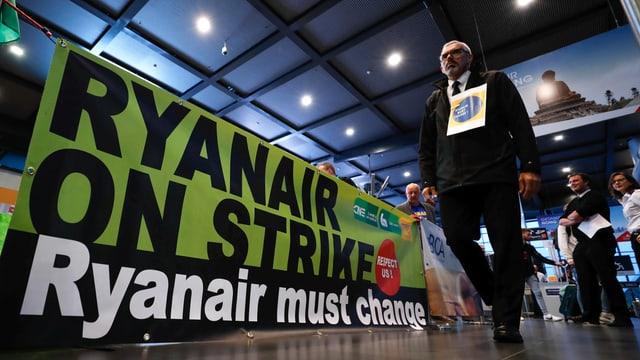 Pilot mit Schild um den Hals läuft an einem Plakat vorbei. Darauf steht: Ryanair on Strike. Ryanair must change.