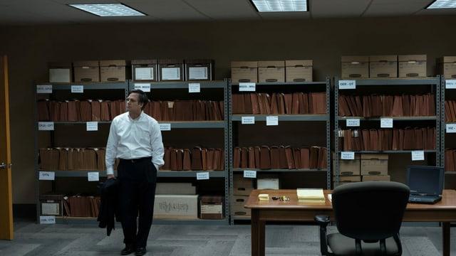 Ein Mann vor Archivmöbeln.