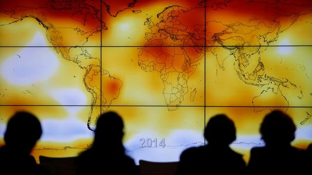 Teilnehmer der Pariser Klimakonferenz im Dezember 2015 vor einer Weltkarte der Klimaanomalien