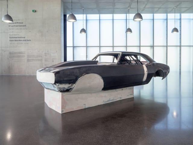 Ein schwarzes Auto steht unter vielen Lampen im Museum.