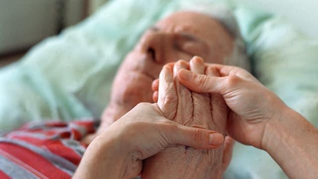 Alter Mann liegt in Spitalbett, Pflegerin hält seine Hand