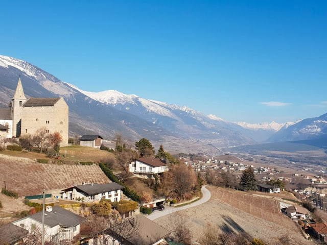 Blick auf ein Tal mit einer Kirche im Vordergrund.