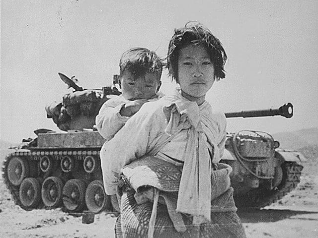 Koreanisches Mädchen steht vor einem Panzer und trägt einen Jungen auf dem Rücken.