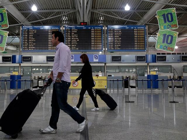 Zwei Passagiere laufen durch die Wartehalle eines Flughafens